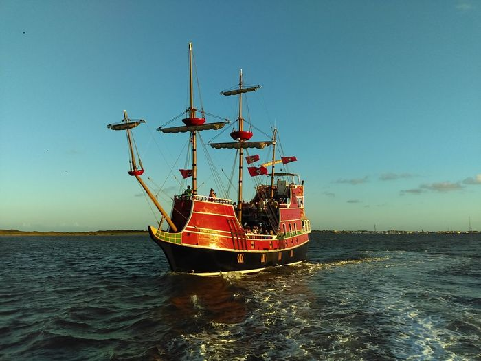 Red dragon pirate cruises on sea against sky