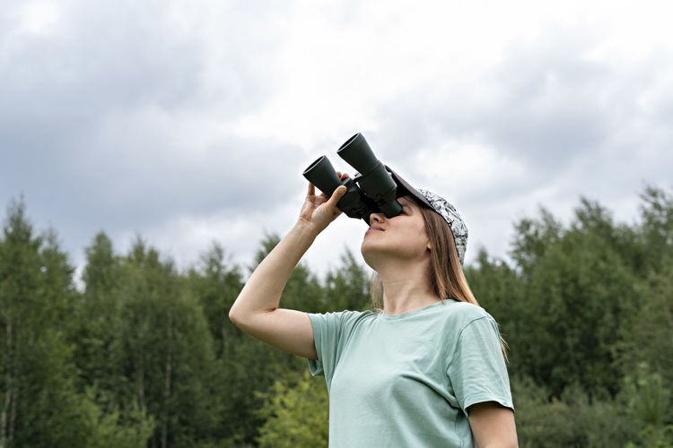 Young blonde woman bird watcher in cap  looking through binoculars cloudy sky in forest ornithology