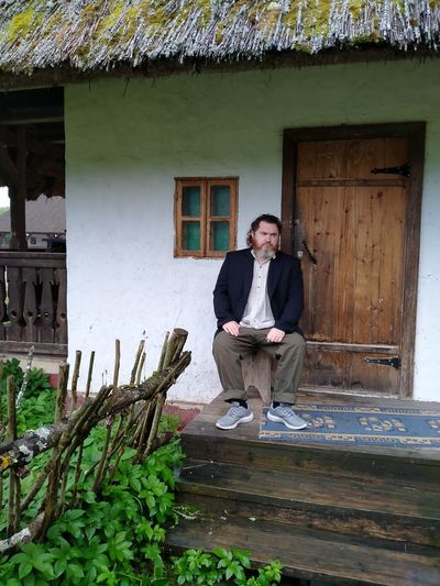 Portrait of smiling man standing outside house