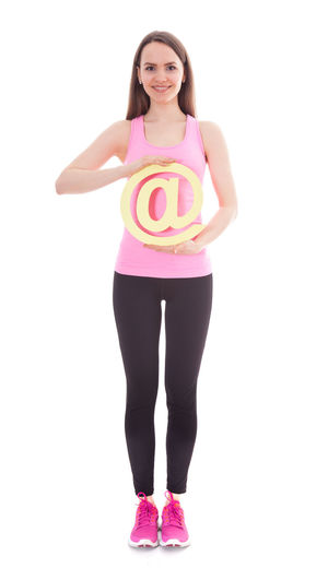Athletic girl holding at sign. All on white background At Sign Athletic Athletic Female Front View Full Length Gym Happy Face Internet Isolated On White Leggings Online  Smiling Sports Wear Sporty Girl Studio Shot Training Web White Background White Backround Workout