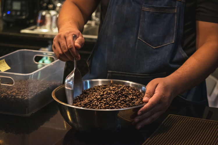 Midsection of barista preparing food in cafe
