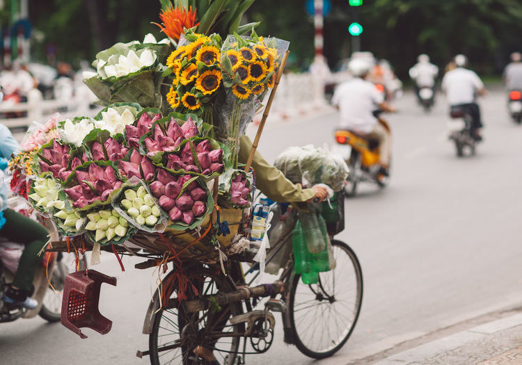 Rear View Of Man Selling Bouquets On Bicycle At Street