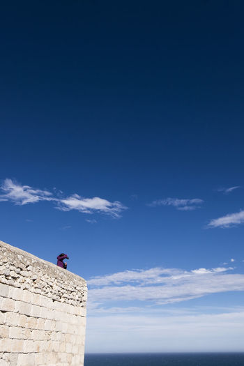 Low angle view of woman on fortified wall against blue sky