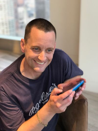 Portrait of happy man using mobile phone at home