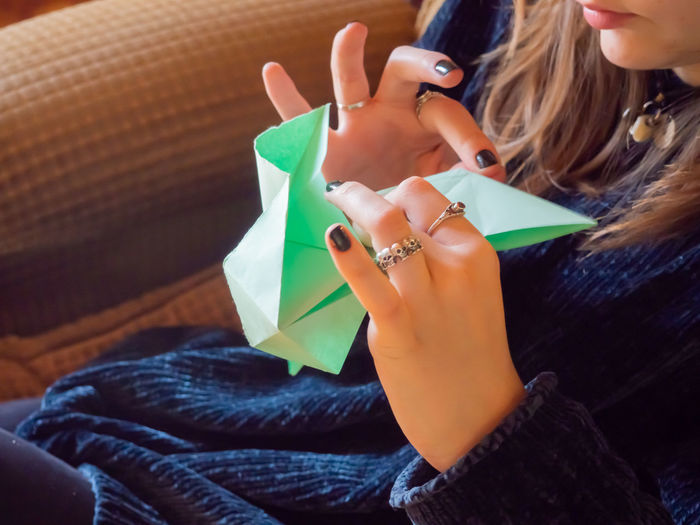 Midsection of woman making paper boat while sitting on sofa at home