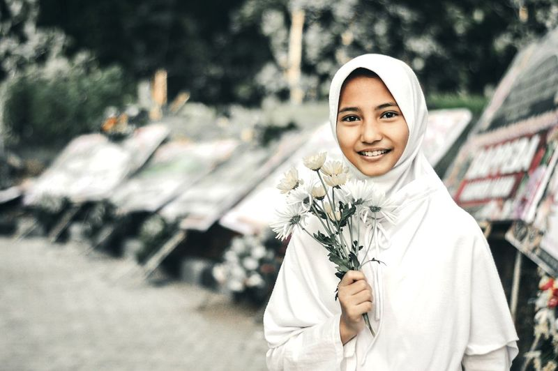 Portrait of smiling girl wearing white hijab holding flowers on street