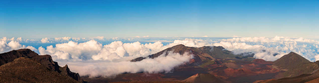 Panoramic view of mountains with cloudscape against clear sky