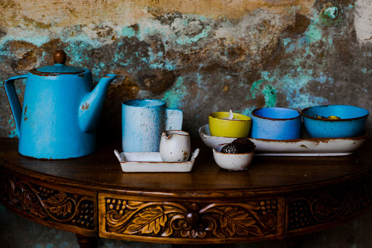 Close-up of crockery on table against wall