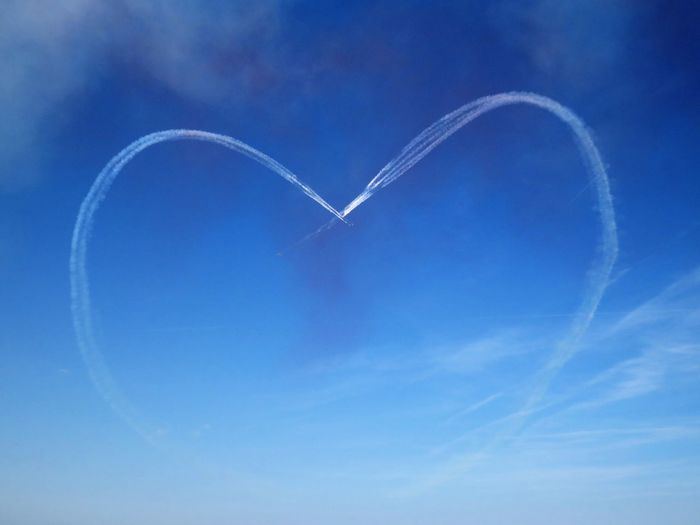 Low angle view of vapor trails forming heart shape in blue sky
