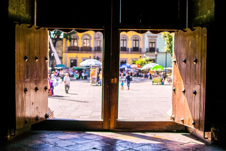 People on city street seen through open wooden window