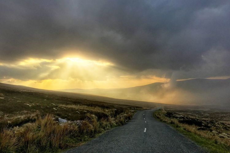 Empty Road Amidst Field Against Cloudy Sky During Sunset
