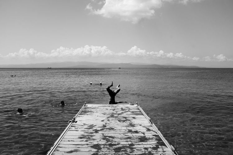 Man standing at sea shore against sky