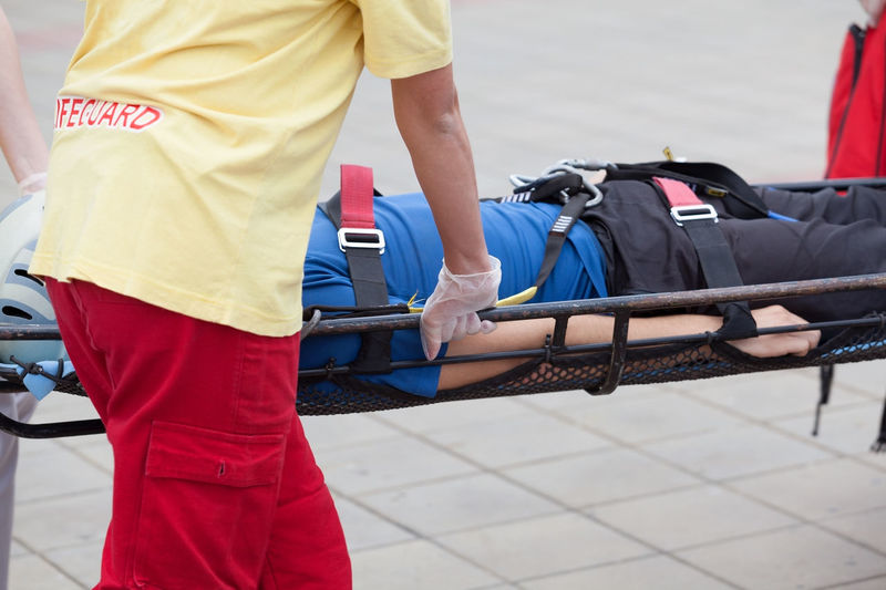 Midsection Of Man Carrying Patient On Stretcher