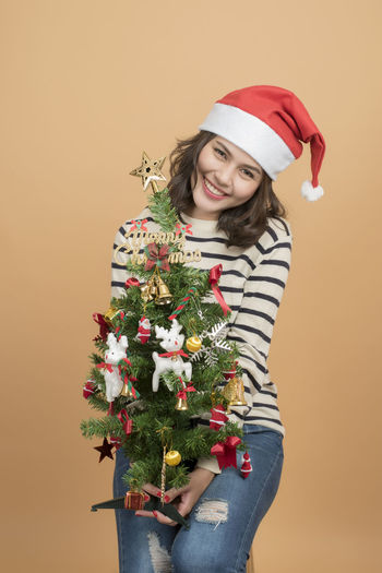 Portrait of young woman holding christmas tree against beige background