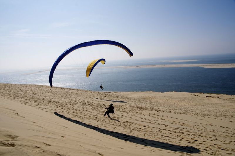 Silhouette People Paragliding At Beach Against Sky