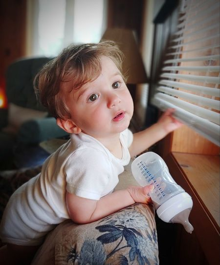 Cute baby girl sitting by window at home
