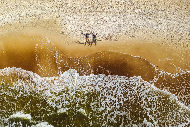 Drone View Of Couple Lying On Sand At Beach