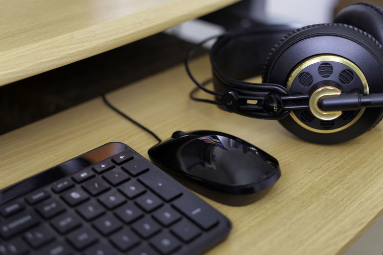 Close-Up Of Computer Keyboard And Headphones On Table