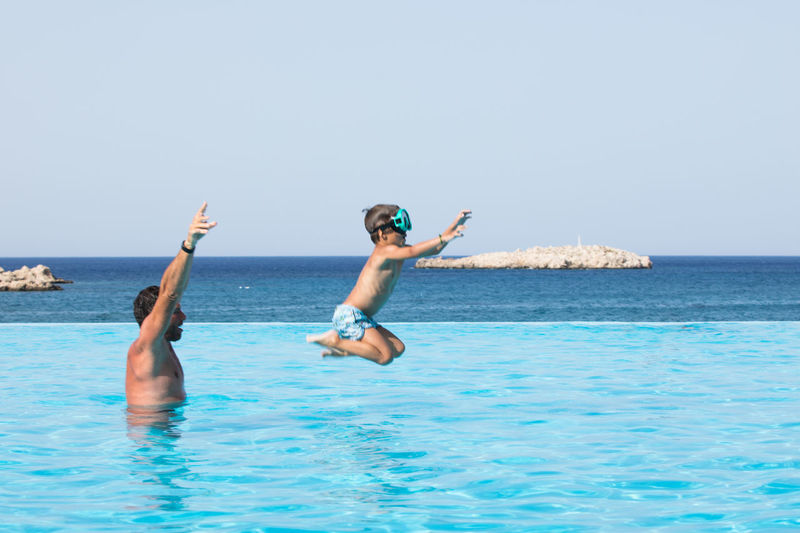 Man playing with son in infinity pool