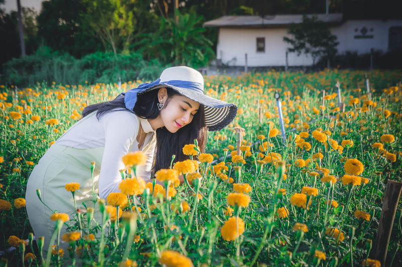 Young woman wearing hat while smelling flowers on field