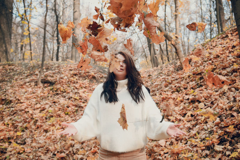 Young woman standing with autumn leaves in forest
