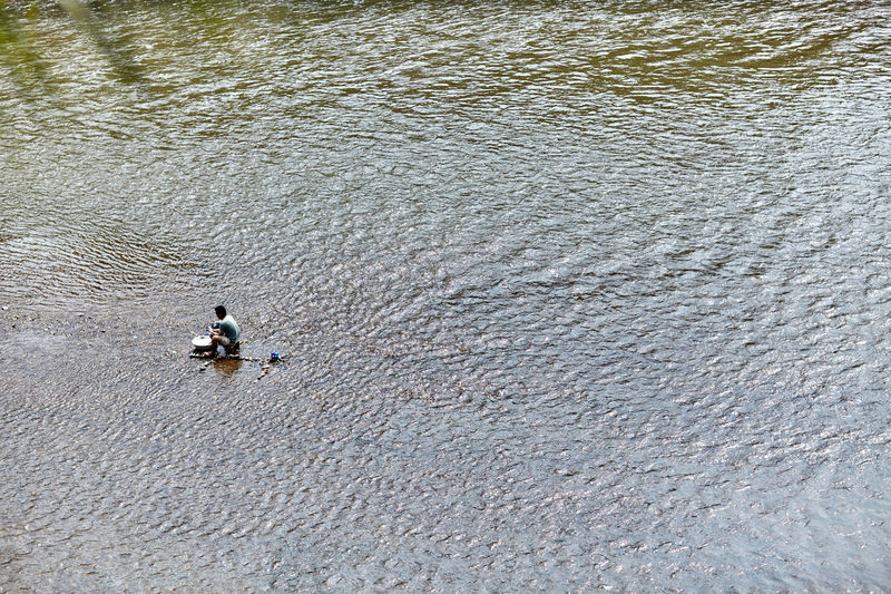 High angle view of man sitting in river