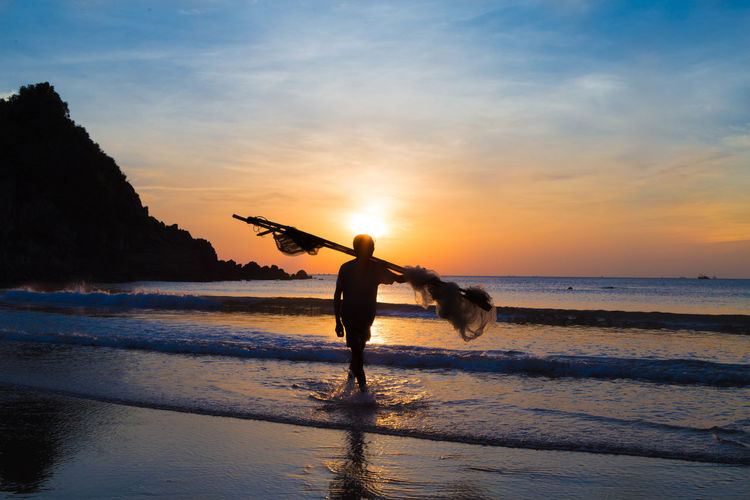Sunset Beach Water Sea Silhouette One Person Full Length People Outdoors One Man Only Adult Nature Summer Vacations Standing Men Only Men Beauty In Nature Adults Only Sky