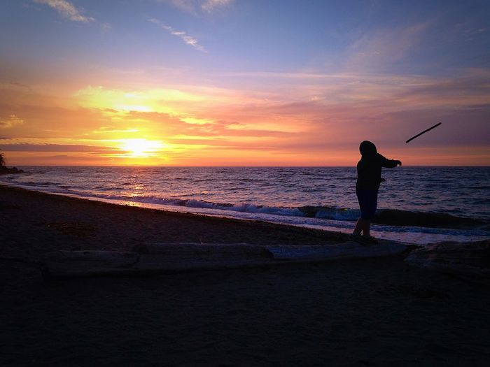 Person Throwing Stick In Sea Against Sky During Sunset