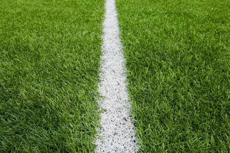 green grass American Football Field Backgrounds Competition Competitive Sport Day Grass Green Color High Angle View Land Nature No People Outdoors Plant Playing Field Single Line Soccer Soccer Field Sport Textured Effect Turf White Color