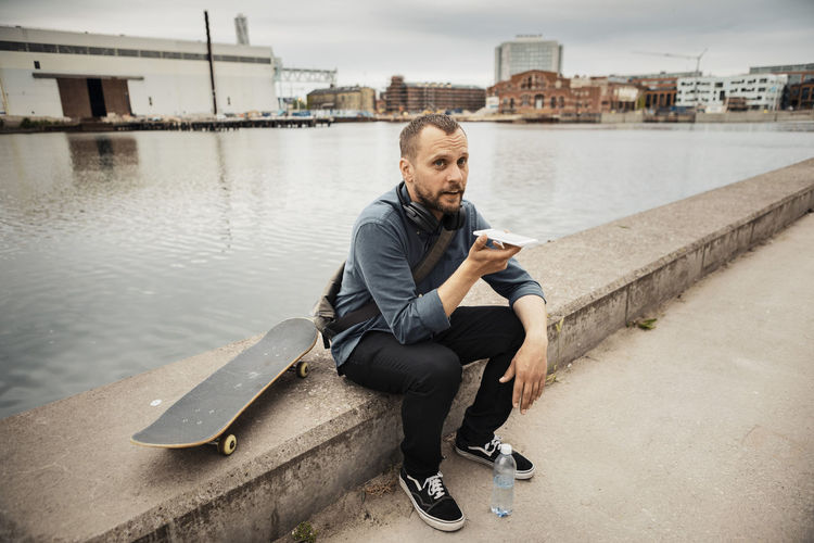 Full length portrait of young man sitting on mobile phone in water