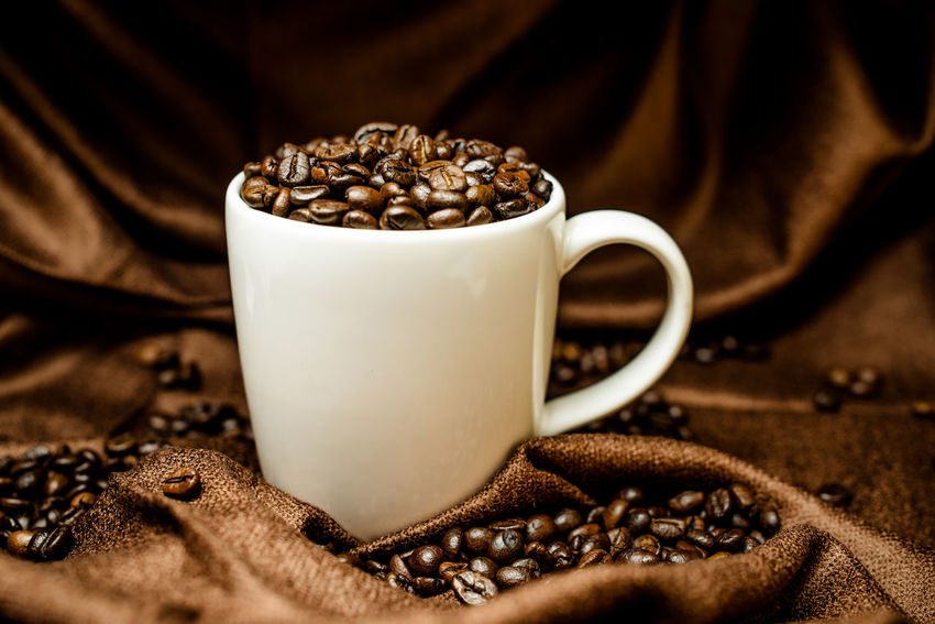 Cup of full roasted coffee beans, studio shot Brown Cappuccino Close-up Coffee - Drink Coffee Bean Coffee Cup Day Drink Food Food And Drink Freshness Frothy Drink Indoors  Mocha No People Raw Coffee Bean Roasted Roasted Coffee Bean Sack Scented Still Life Textile