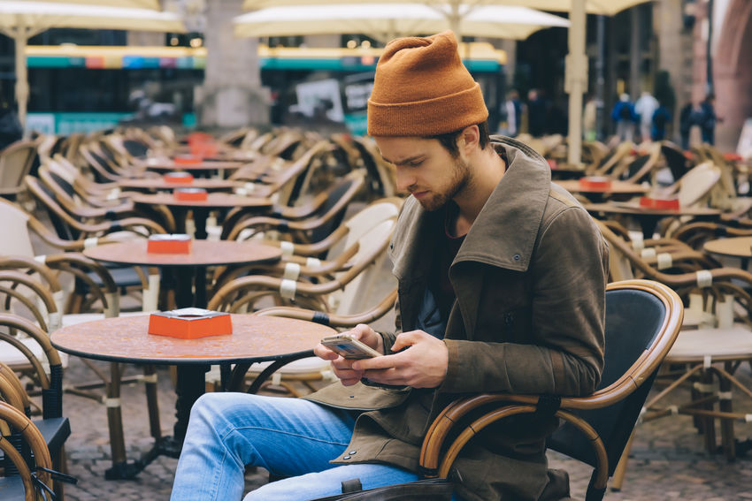 young men in the city with a mobile phone Adult Adults Only Authentic Moments City Day Gemany  Hat Hipster Knit Hat Leipzig Lifestyles Men One Man Only One Person Only Men Sitting Technology Warm Clothing Wireless Technology Young Adult