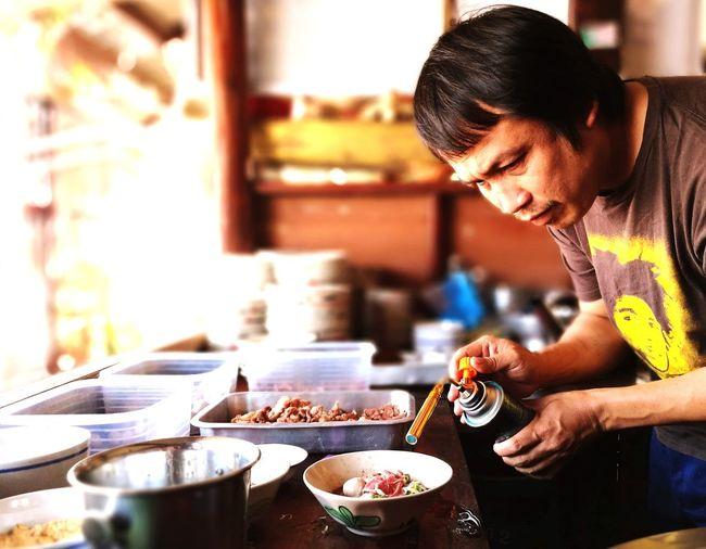 Mature man preparing food with butane torch in kitchen