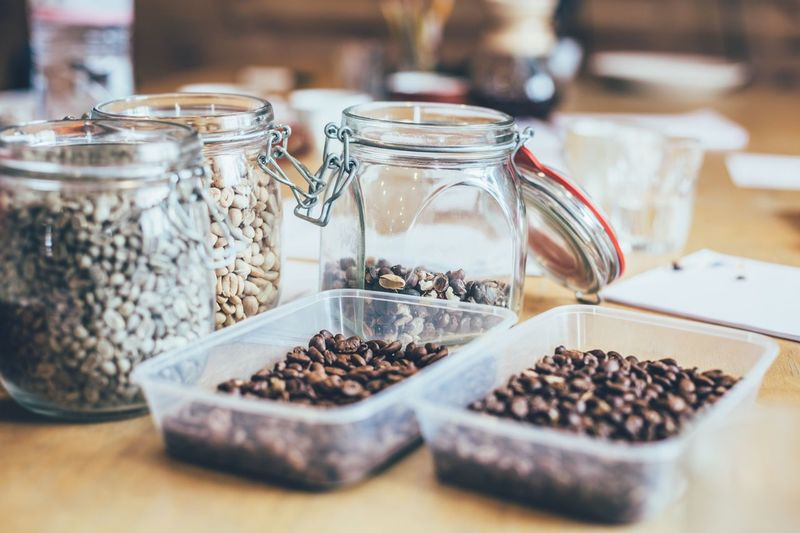 Roasted coffee beans in containers on table