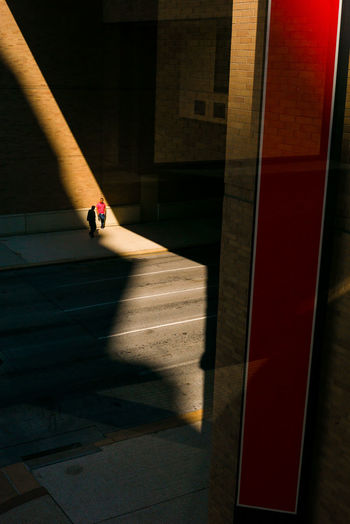 Shards of light on Houston streets light up a pedestrian Texas Sunlight Street Shadow Shadow And Light Red Street Scene Reflection