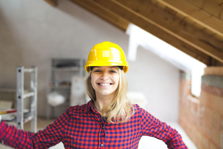 Portrait of smiling woman in helmet at construction site