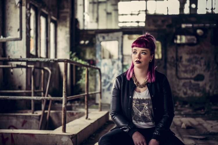 Woman looking away sitting in abandoned building