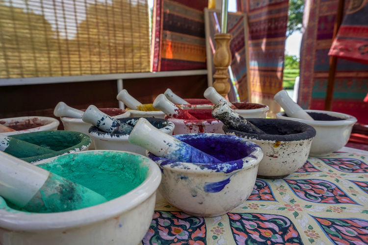 Close-up of powder paint in containers on table