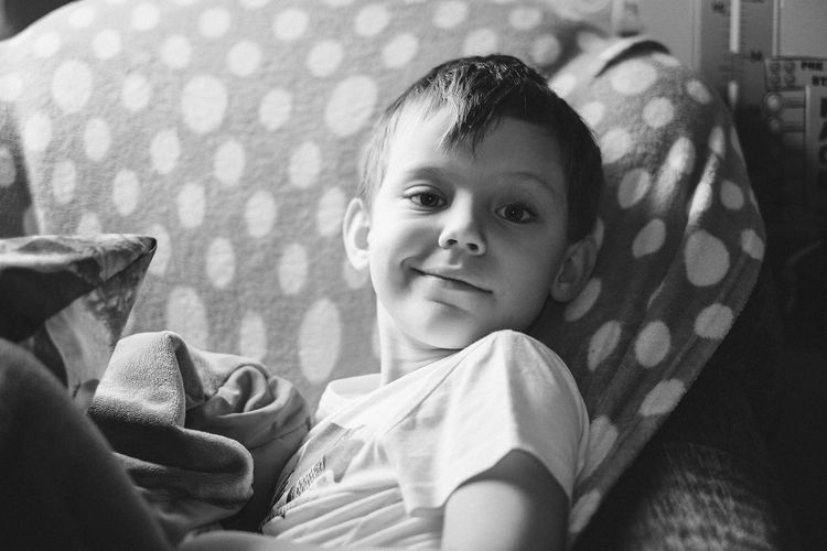 Portrait of boy smiling while lying on bed at home