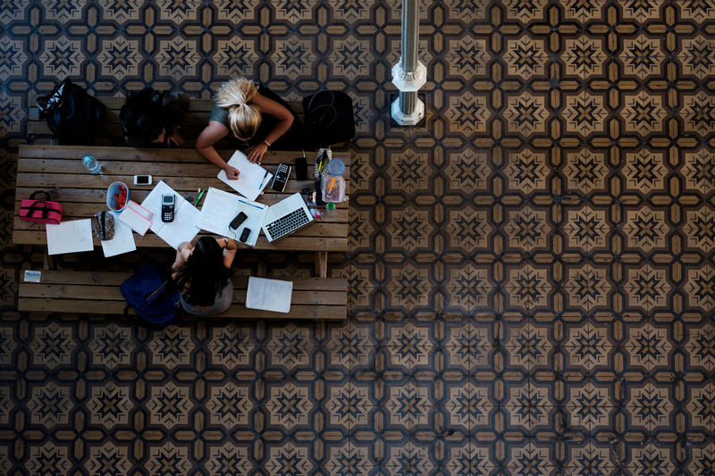 Directly Above Shot Of People Studying At Desk On Tiled Floor