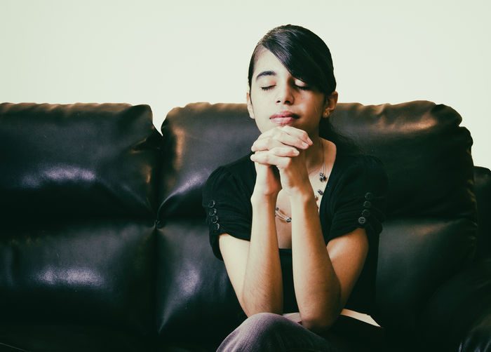 Christian faith: Real life female teenager praying at home Christian Christianity Devotional Faith Meditation Belief Believe Bible Front View Hands Clasped Indoors  Instagramesque Lifestyles One Person People Prayer Praying Real People Religion Religious  Reliion Sitting Sofa Young Adult Young Women