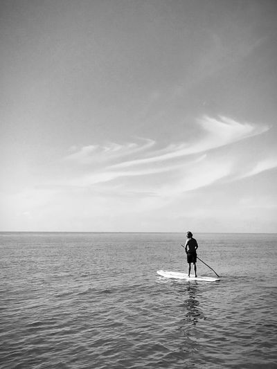 Rear view of man paddleboarding in sea against sky