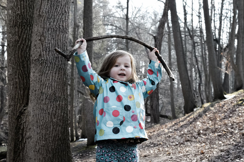 Portrait Of Cute Girl Holding Stick Aloft In Forest