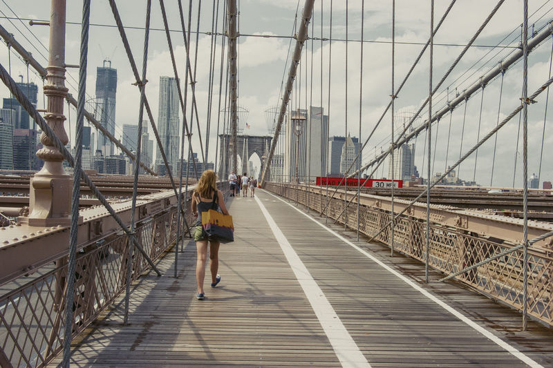 Female pedestrian walking the Brooklyn bridge after a day of shopping Carrying Shopping Architecture Bridge Bridge - Man Made Structure Built Structure City Connection Day Full Length Lifestyles One Person Outdoors Real People Sky Suspension Bridge The Way Forward Transportation Travel Young Adult