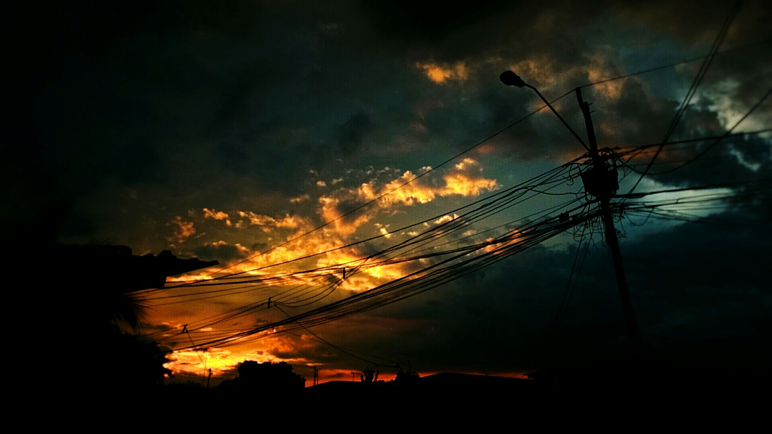 sunset, silhouette, power line, power supply, electricity, low angle view, cable, connection, sky, tree, scenics, beauty in nature, tranquil scene, orange color, electricity pylon, cloud, outdoors, nature, tranquility, cloud - sky, power cable, atmospheric mood, majestic, outline, dramatic sky, atmosphere, back lit, cloudscape
