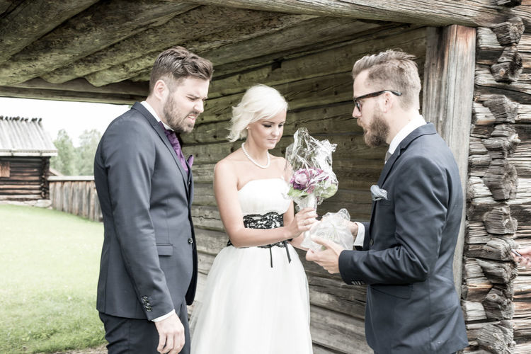 Friend Gifting Bouquet To Bride And Groom By Wall
