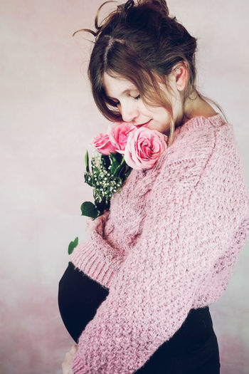 Close-up of woman holding pink rose