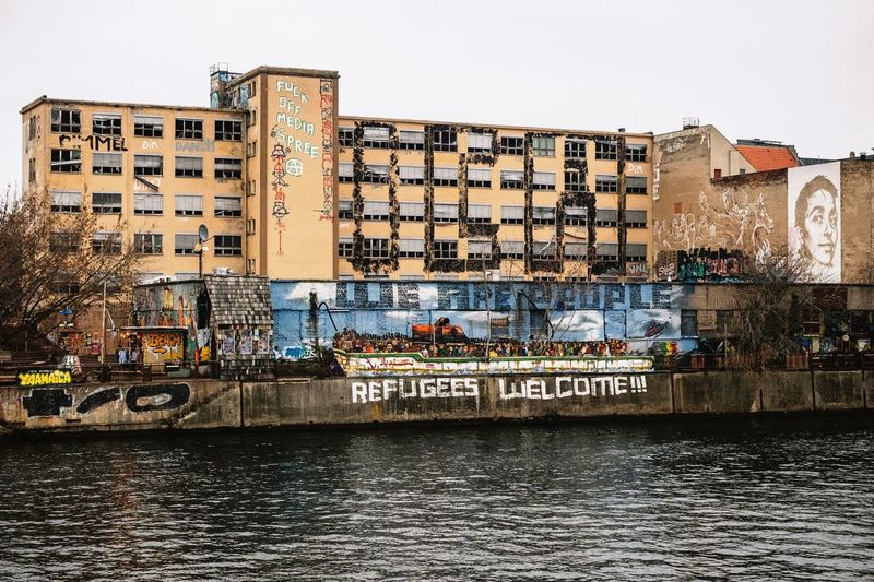 Building Exterior Architecture Built Structure Water Sky Waterfront Nautical Vessel Outdoors No People Day City Nature Streetphotography Street Art Graffiti Capture Berlin Germany Berlin Riverside Street Art/Graffiti Finding New Frontiers