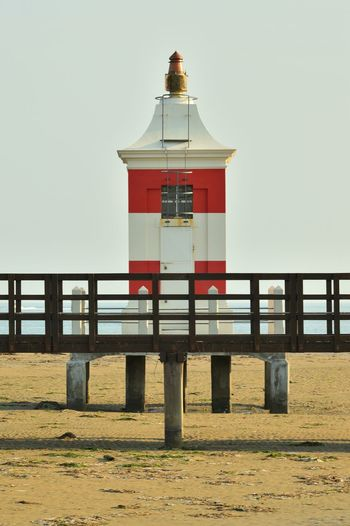 Lighthouse by building against clear sky