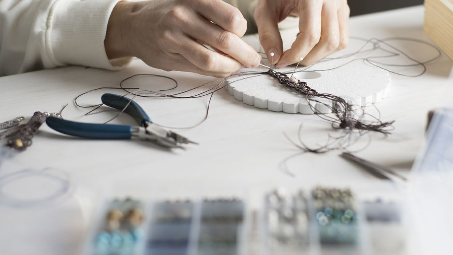 Close-up of woman working with thread on table
